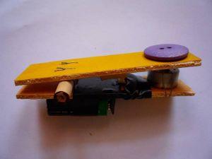 Chiudendo a fondo i due listelli, la tacca di legno preme l'interruttore e aziona il motorino che fa girare il bottone